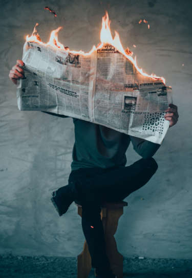 Person Reading Newspaper that is on fire